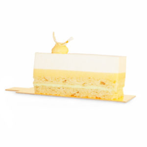 Slice of layered mousse, lemon curd, mint cream and almond sponge cake