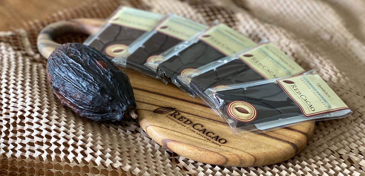 A selection of single original chocolate blocks neatly layed out next to a cacao pod